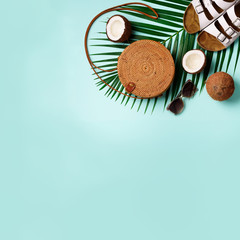 Round rattan bag, coconut, birkenstocks, palm branches, sunglasses on blue background. Square crop. Top view, copy space. Trendy bamboo bag and shoes. Summer fashion flat lay. Trip, vacation concept