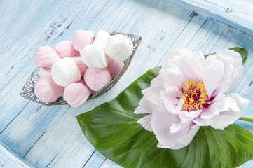 Marshmallows in a vase next to peony flower on a green leaf on a light wooden background.