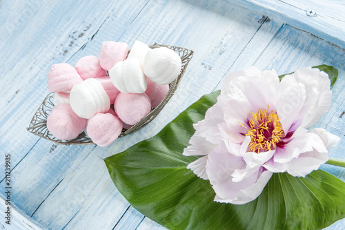 Marshmallows In A Vase Next To Peony Flower On A Green Leaf On A