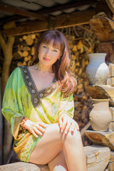 Ethnic middle age hippie woman posing in boho style clothes at nature. Outdoor fashion. Concept of boho style and etno