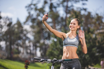Smiling athletic lady is having fun while cycling in park. She is holding smartphone at arm length both smiling and waving hello to camera. Female is taking snapshot of herself