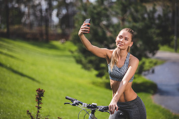 Happy young woman is taking picture of herself while riding bike. She is smiling while looking at camera. Female is spending active day in the nature