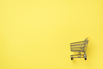 Shopping cart on yellow background. Minimalism style. Creative design. Top view with copy space. Shop trolley at supermarket. Sale, discount, shopaholism concept. Consumer society trend