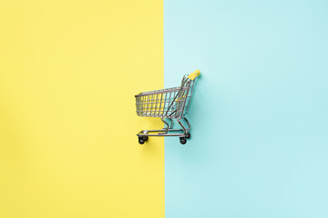 Shopping cart on blue and yellow background. Minimalism style. Creative design. Top view with copy space. Shop trolley at supermarket. Sale, discount, shopaholism concept. Consumer society trend