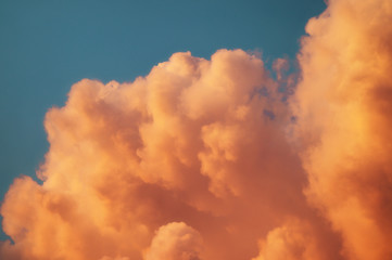 Blue sunset sky with texture of rare beautiful evening cumulus clouds in light of setting sun for designer's background