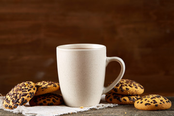 White cup of tea and cookies on a log over country style wooden background, close-up, selective focus