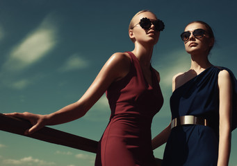 Two fashion models pose against the background of the Sunny sky Wall mural