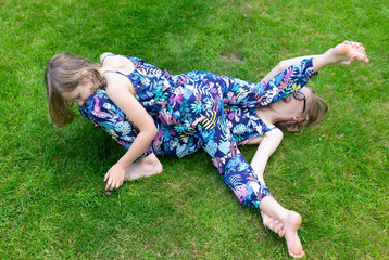two sister on the grass playing and having fun