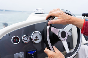 hand steering a motor cruiser on the sea