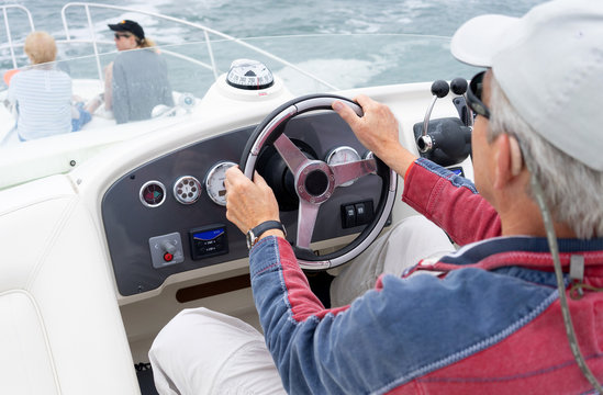 man driving a motor cruiser on the sea