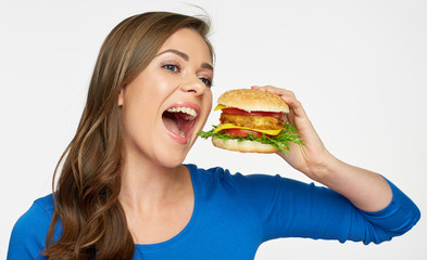 Smiling woman eating fast food burger.