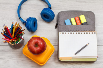 Lunch box, apple, pencils, headphones and open exercise book on bag-pencil case with color felt pens and marker on grey background
