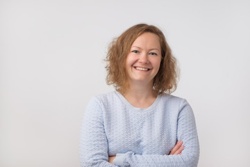Smiling european lady in blue sweater looking at camera, isolated on gray background.
