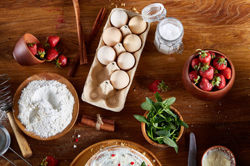 Strawberry tart covered with whipped sour cream surrounded by organic ingredients over wooden background, flat lay.