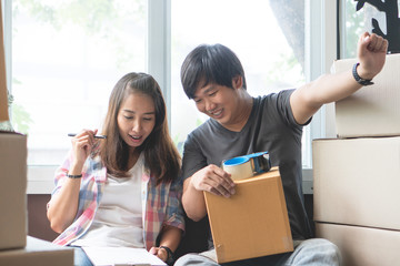 Concept young couple moving house. Asian woman holding box of stuff ready for relocation and husband is packing stuff into cardboard box prepare to move.