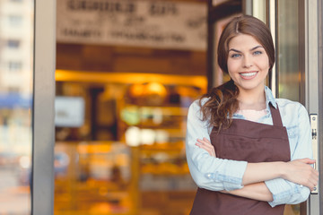 Poster de jardin Boulangerie Smiling owner in uniform in the bakery