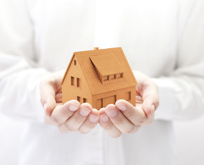 Small orange house in hands