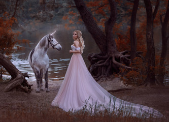 The princess met a unicorn in the forest. The blonde girl with a gentle make-up, is dressed in a long vintage dress with a lush skirt and train. Artistic Photo