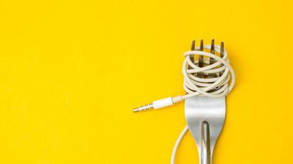 Forks and earphones on yellow background.Food sing symbol Fotoväggar