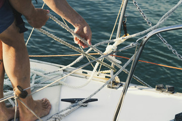 man pulls the cables to anchor the yacht in the port