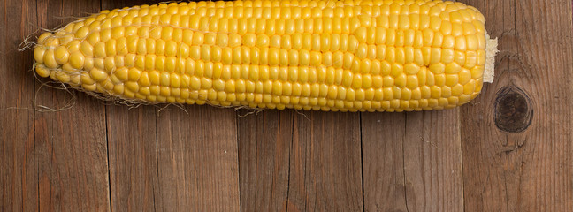 Wall Mural - banner corn on the wooden background