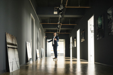 Businessman riding longboard and using cell phone on office floor