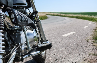 Classic vintage motorcycle along a curvy road in the countryside.