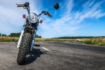 Classic vintage motorcycle along a curvy road in the countryside. Blue sky and farmers field.
