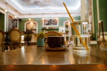 Cup of cappuccino and glass of water on the table, coffee shop background, warm tone