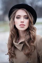 Pretty girl in black hat outdoors, portrait