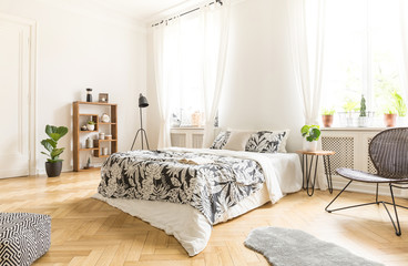 Black chair near bed with patterned sheets in white bedroom interior with pouf and fur. Real photo