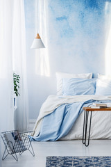 Books on table and white and blue bedding on bed in pastel bedroom interior with lamp