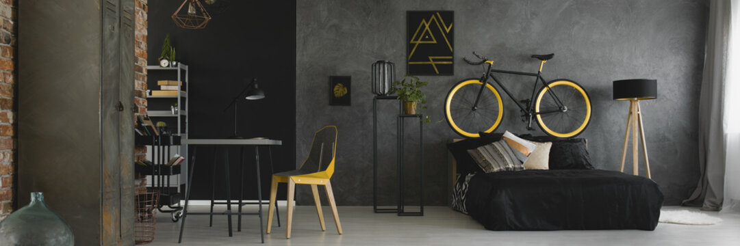 Dark studio flat interior with texture grey wall, black and yellow bike standing on bedhead, desk with geometric chair and double bed with black bedding