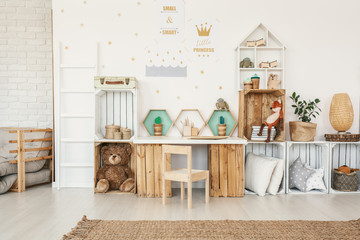 White kid room interior with gold posters on the wall, toys and pillows placed on crate shelves and desk with artificial cactuses