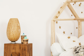 Two artificial cactuses and wicker lamp standing on wooden bedside table in white kid room interior