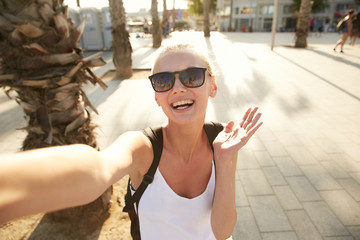 A girl making an emotional selfie on a street of Barcelona