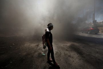 Palestinian girl stands amongst smoke during clashes with Israeli troops at a protest near the Jewish settlement of Beit El, near Ramallah, in the occupied West Bank