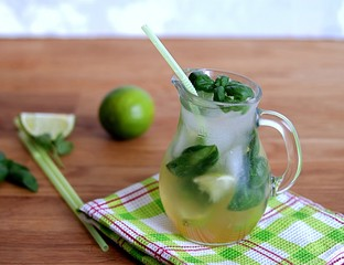 Cold summer drink, lemonade with lime and basil on the basis of sparkling water and sugar syrup in a small glass jug. Served with ice. Summer concept.