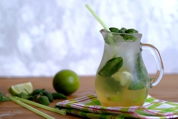 Cold summer drink, lemonade with lime and basil on the basis of sparkling water and sugar syrup. Served with ice. Summer concept.