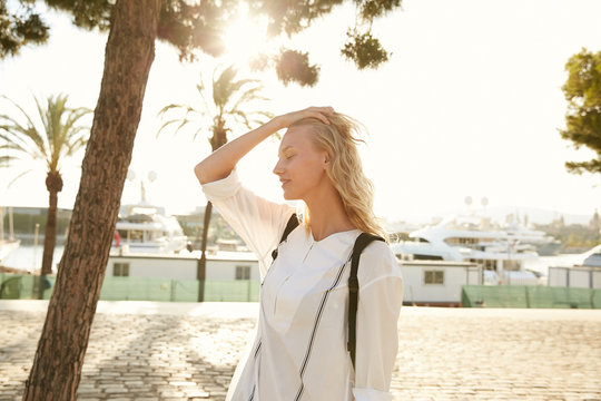 Portrait of a model blond girl walking around Barcelona coast with dock and yachts under the palms