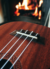 Ukulele small guitar close up stings, fireplace on the background. Musical concept, guitar fret board macro, fire in chimney, cosy romantic atmosphere.