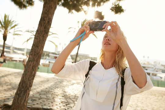 A girl taking a photo with a little camera in Barcelona in front of palms