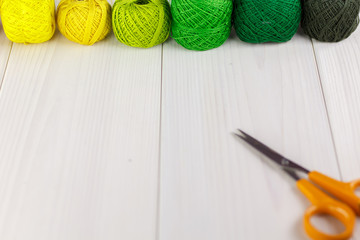 Rainbow-colored embroidery yarns with scissors on a wooden table.