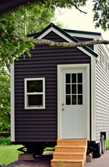 Tiny gray house on wheels in a closeup portrait view