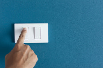 A finger turning on lighting switch on rough on blue dark wall.