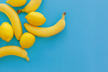 yellow bananas and lemons on bright blue paper, trendy flat lay. fruits modern image, top view. juicy summer vitamin abstract background. pop art style. minimalism. space for text