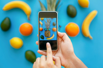 hands holding phone and taking photo of pineapple in sunglasses and bananas, oranges and avocado on blue paper, trendy flat lay. stylish food photography. instagram fruit photo