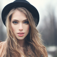 Nice young woman in hipster hat outdoors, portrait