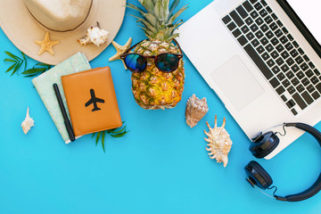 summer vacation concept, flat lay. laptop, pineapple in sunglasses, passport, map, hat, headphones on blue trendy paper with shells. space for text. travel and wanderlust