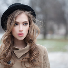 Attractive young woman with wavy hairstyle outdoors, portrait